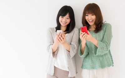 attractive asian women using smart phone in the room